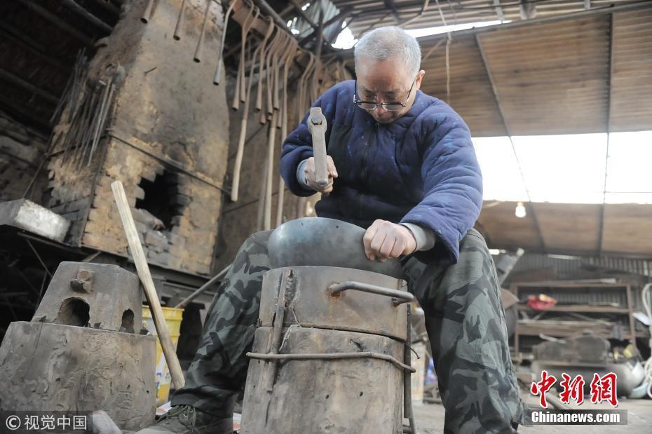 铁匠传承人牛祺圣在家里制作铁锅.图片来源:视觉中国